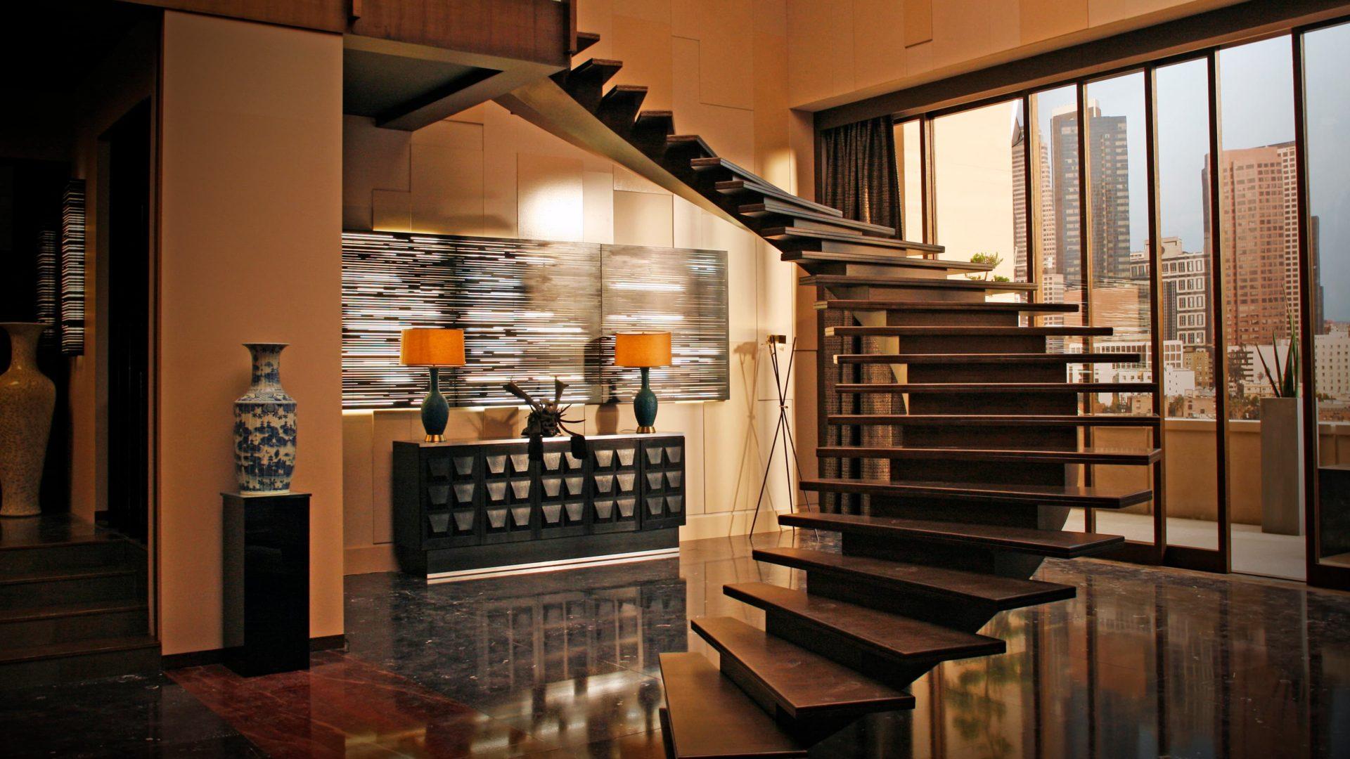 Dans un appartement lumineux et moderne, un escalier balancé majestueux. L'escalier du film Taken 3.