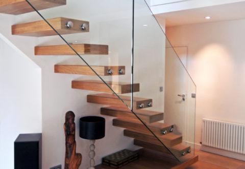 Un escalier autoportant avec des marches bois et un garde-corps en verre.