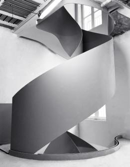 Photographie d'un escalier en spirale réalisée dans le courant de l'année 2020 chez un particulier à Paris. Un étage de l'escalier vu de face, avec des courbes élégantes.